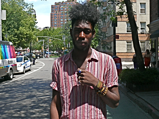 Olu Alege in a Basque stripe tunic accessorized with Buddhist beads and blue stone rings on Bleeker Street in the West Village
