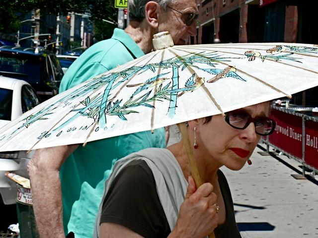 Staying cool and incognito under an Asian parasol with a summer scarf in Chelsea