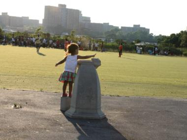 A girl tries to summon water from a non-working fountain at Ferry Point Park's 3-year-old synthetic-turf soccer field. Besides a working water fountain, the large park also lacks a restroom.
