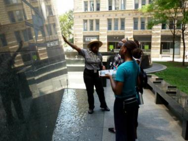 A National Park Service ranger describes the history of the African Burial Ground National Monument during a tour.