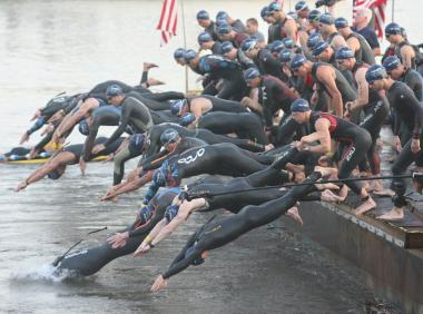 Pros enter the water at the swim start of the Aquaphor New York City Triathlon on Sunday, July 8, 2012.