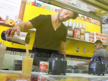 Fotis Blanis, the manager of Banana Queen in Mount Eden, pours a fresh-made smoothie specially designed to beat the heat.