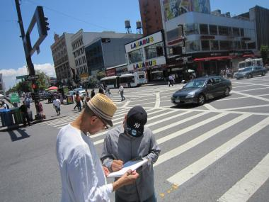 Julius Tajiddin, founder of the grassroots group Preserve Harlem's Legacy, collects signatures at Adam Clayton Powell Jr. Boulevard and 125th Street to stop planned DOT safety changes to the boulevard such as narrowing the lanes.