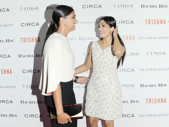 Rachel Roy and Freida Pinto, seemingly discussing their ponytails, at the Cinema Society screening of