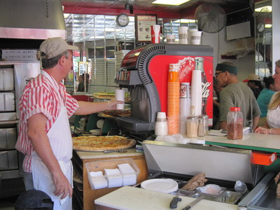 The manager of Sam's Famous Pizza fills a large cup with fountain soda for a customer.