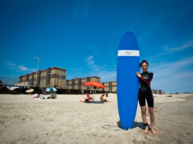 Akemi Tatsuta, 27, from Astoria with her surf board before heading to the beach.