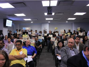 Several dozen protestors stood in the back of the room with signs urging the commission to raise the fare.