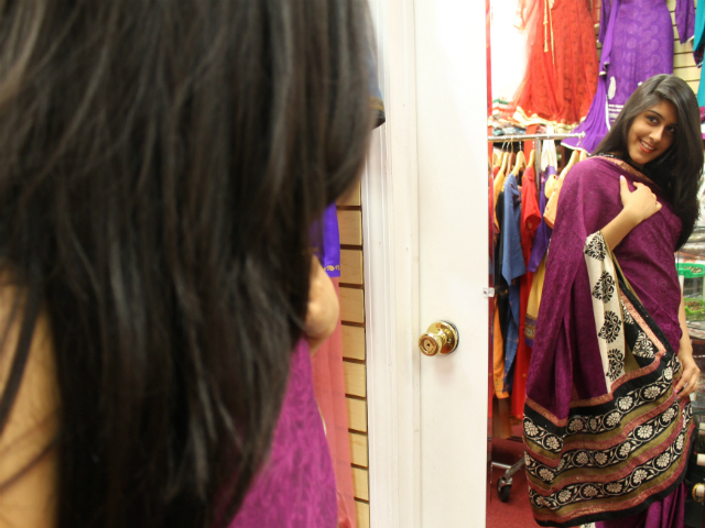 Mariam Shabbir, 19, checks out a grape colored chiffon sari.