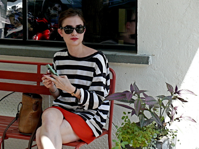 Taking a pause from the activity in the shade in a very stylish black and white stripe knit and a red skirt.