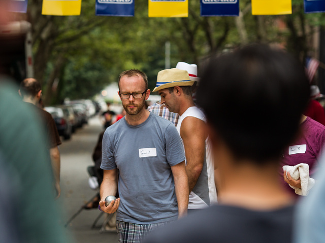 A player lines up his shot during a game of petanque at Bastille Day in Brooklyn on July 15th, 2012.