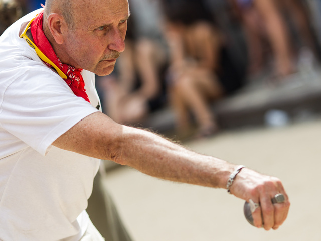 A player prepares his shot during a game of petanque at Bastille Day in Brooklyn.