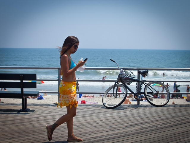 A girl walks on the boardwalk of Rockaway Beach.
