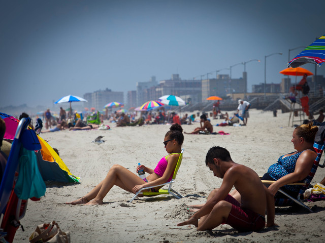 "Sierra Figueroa, 12, (in red) from South Ozone Park said she came almost daily to the Rockaway Beach. ""It's a nice beach here,"" said Figueroa as she tanned by the sand with her family on July 16."
