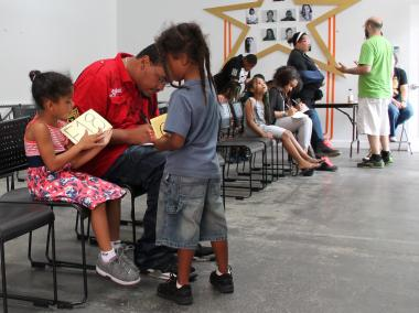 James Gor, 30, red shirt, helps his cousins, Hypolytus Lourens and Cayla Lourens, fill out forms at the casting call Friday, July 13, 2012.