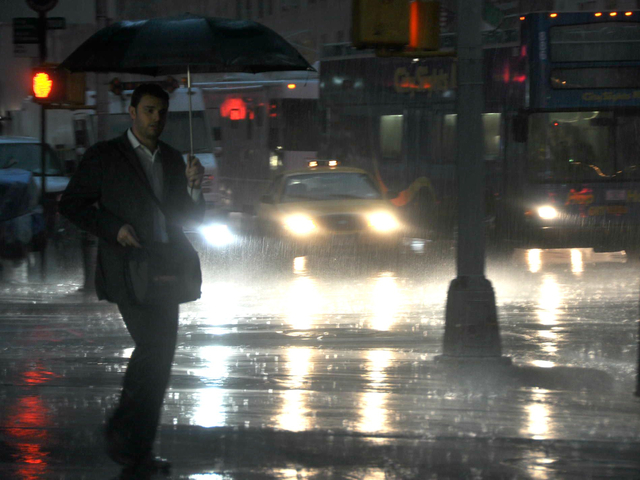 A man walked through torrential rains in midtown on July 18, 2012 as the Office of Emergency Management issued a flash flood warning for New York City through rush hour.