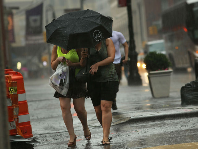 People walk through the rain during an intense afternoon thunderstorm on June 22, 2012 in New York City. The storm brought relief to two days of oppressively hot weather in New York and much of the East Coast where high heat warnings and air quality alerts had been issued from Quebec to Virginia.
