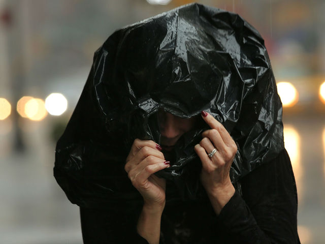 A woman walks through the rain during an intense afternoon thunderstorm on June 22, 2012 in New York City.