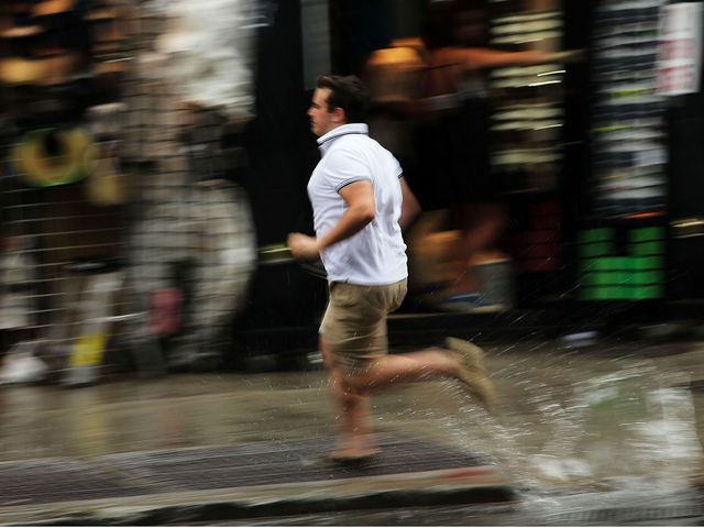 A man runs through the rain during an intense afternoon thunderstorm on June 22, 2012 in New York City.