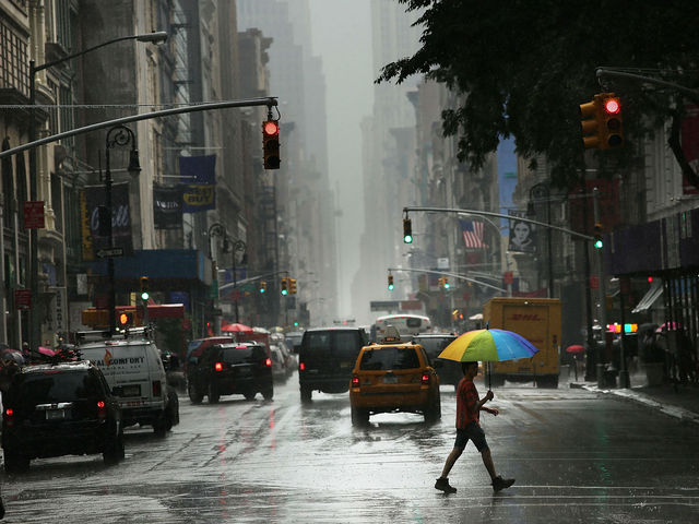 A man walks through the rain during an intense afternoon thunderstorm on June 22, 2012 in New York City.