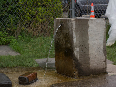<p>A spring user built a concrete structure that houses the pipe. The water flows constantly, some believing it comes from Pennsylvania before reaching the Island.</p>