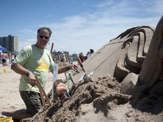 Professional Sand Sculptor Matt Long works on a piece commissioned by the Coney Island Redevelopment Corp. on July 21, 2012. Long will judge and run a lighthouse sand building contest at Midland Beach on August 25, 2012.