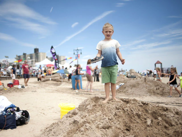 Luka, of Manhattan, stands on a sand pile near his family whose pirate themed sculpture took 1st place in the mixed kids and adults division on July 21, 2012.