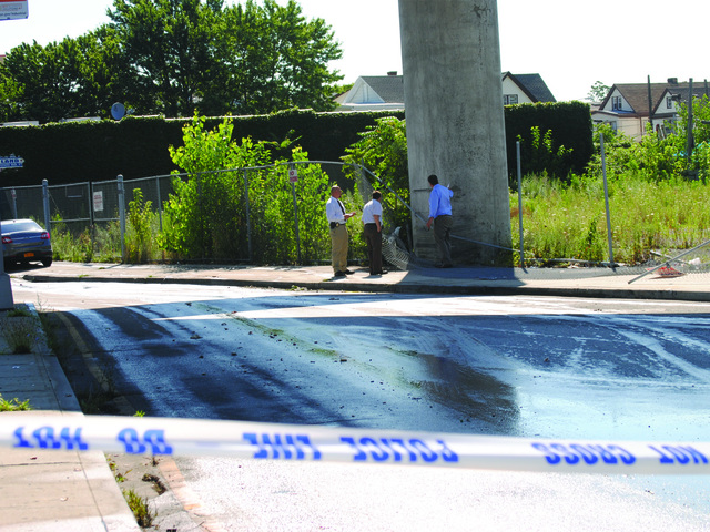 Detectives look over the scene July 22, 2012.
