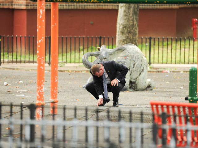 A Detective searches for evidence at the scene where a 4yr old boy was killed on Monday July 23rd, 2012.