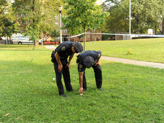 Police Officers search for evidence where 4yr old Lloyd Morgan was shot and killed on Monday July 23rd, 2012.