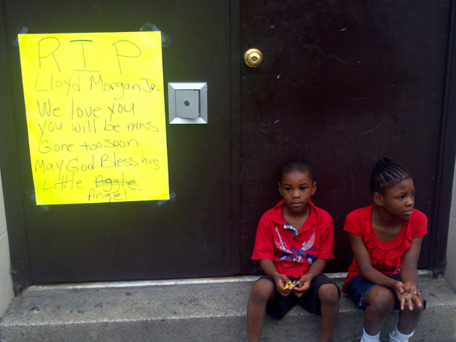 Children sit at a memorial for 4-year-old Lloyd Morgan Monday afternoon, July 23, 2012.