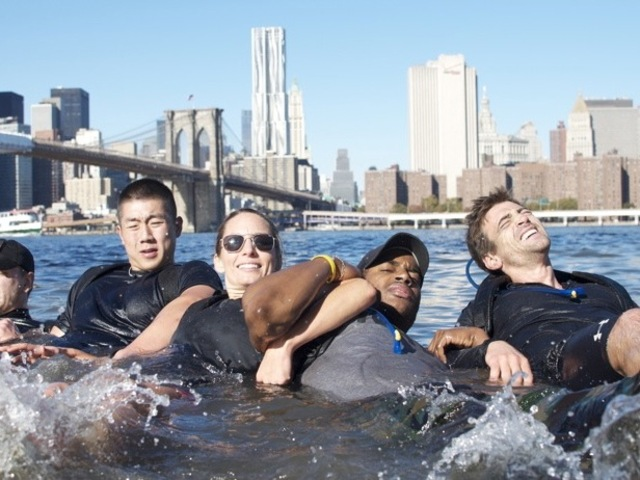 Participants take a linked-arm dip in the East River as part of the Goruck Challenge.