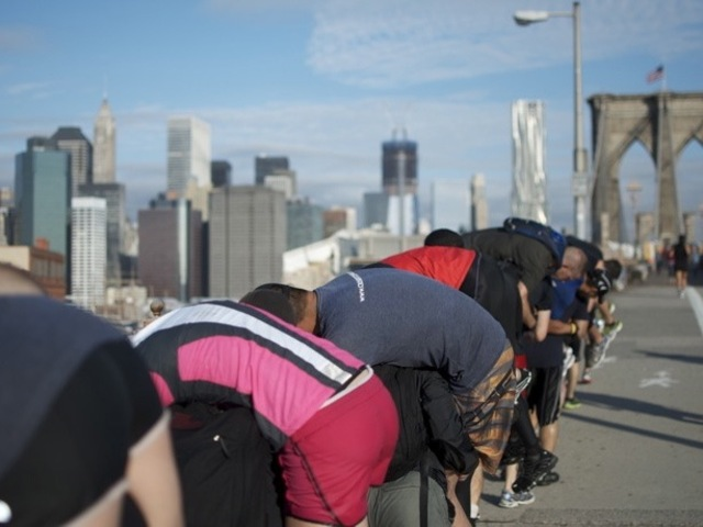 Runners carry one another — and a backpack full of bricks — as part of the Goruck Challenge.