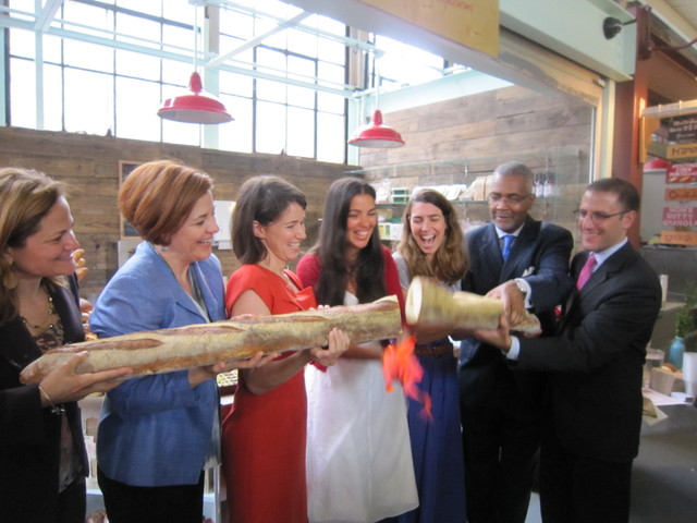 Participants cut a six foot baguette to mark the opening of Hot Bread Kitchen's retail store.