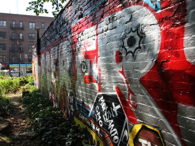 The NYPD dispatched cops with paintbrushes to cover up the controversial mural on the side of an Inwood business on Tuesday, July 24, 2012.