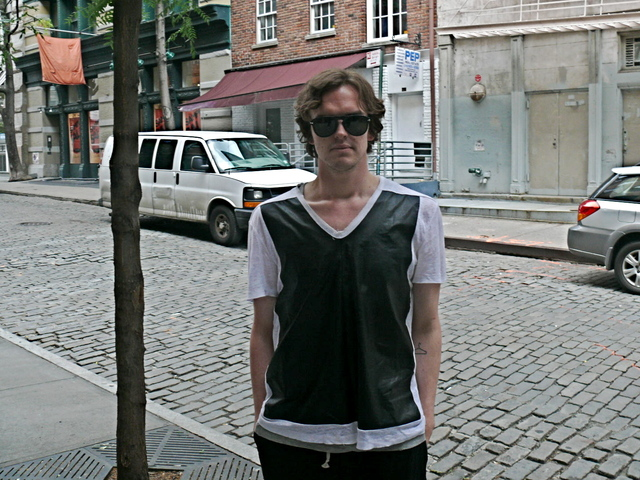 James K. wearing a Neil Barret top made of PVC and sheer cotton with loose easy  pin tucked Rick Owens shorts in SoHo.
