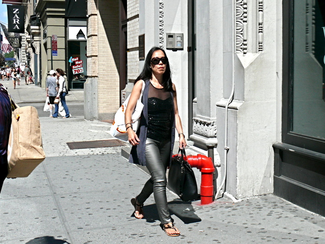 Gun metal black skinny leather jeans worn with a sheer to top with a black paillettes, a large Louis Vuitton textured tote and black and tortoise sandals on Fifth Avenue.