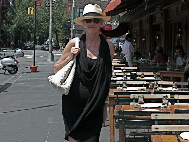 A complex and interesting drape, highlighting the back and shoulders  originating from the  hemline, wraps around the neck into a cowl neck dress paired with a white Bottega Veneta bag and a straw fedora in Greenwich Village