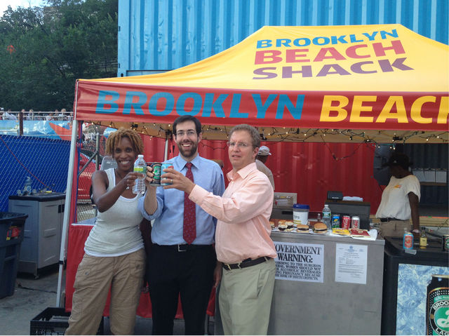 Tracee Loran (manager of the Beach Shack), Senator Squadron, and Glenn Markman toast the new licence.