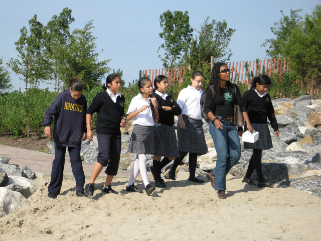 Carter leads a group of students around Barretto Point Park in Hunts Point.