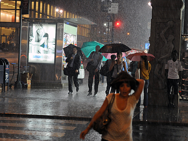 People rushed through the heavy rain near Grand Central Terminal July 26, 2012.