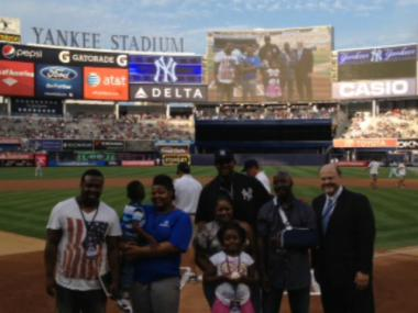 Steve St. Bernard (with arm in sling) stands with his family and MTA chair Joseph J. Lhota at Yankee Stadium on July 31, 2012.