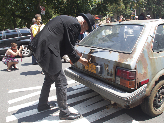 Harry Ettling removes the license plates from his more than 30-year-old car