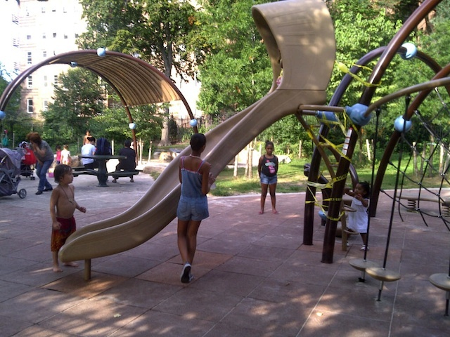 Children play near the newly installed slide at Indian Road playground at Inwood Hill Park.