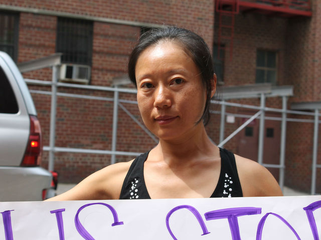 Masako Koga holds a sign protesting the opening of her building to homeless adults. Koga has lived at the SRO for ten years.