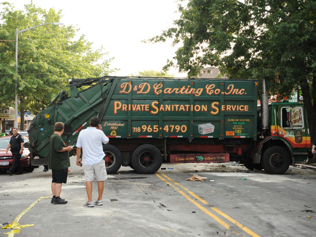 This garbage truck was knocked onto its side by a Jeep SUV early Wednesday morning, Aug. 8, 2012.