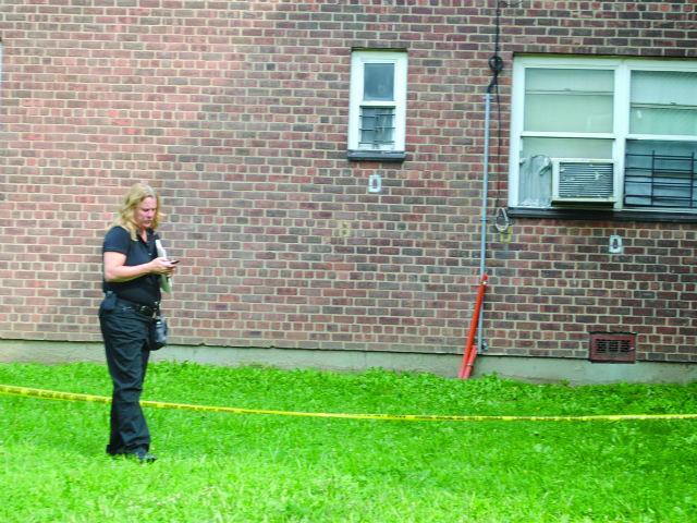 An ACS representative inspects the area where the infant fell on Tuesday, Aug. 7, 2012.