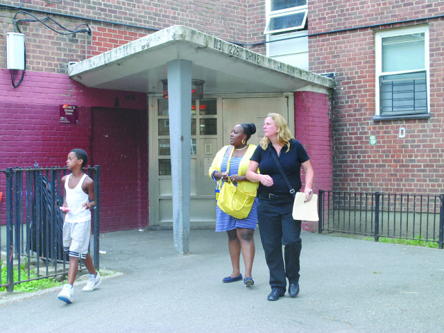 Representatives from ACS leave the building where the infant lives with her family.