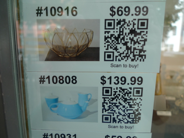 Customers at Robert Henry Vintage scan QR codes with their smart phones to buy items in the window display.