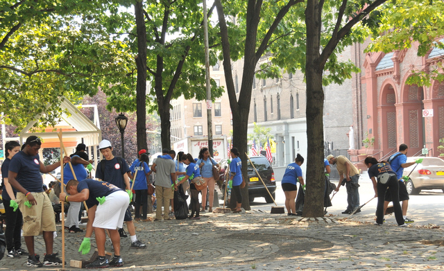 Volunteers clean up during the Northern Manhattan Clean Streets Initiative on August 9, 2012.