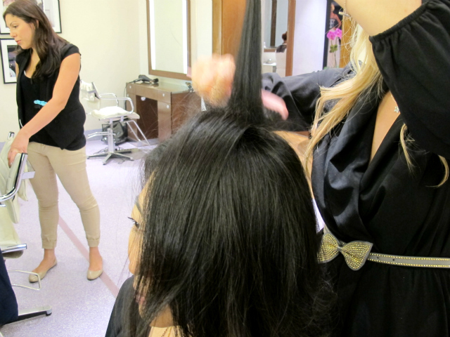 Stylist Kayley Pak begins this ponytail by teasing the hair on the crown of the head to give it some volume.